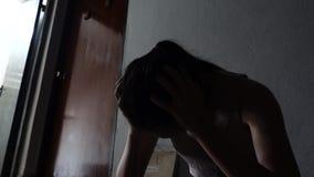 Silhouette d'une jeune fille triste s'asseyant dans l'obscurité se penchant contre le mur dans le vieux logement, violence famili banque de vidéos