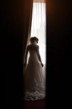 Silhouette d'une jeune mariée à la fenêtre Images libres de droits