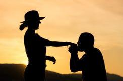 Silhouette d'une main de baiser de monsieur de sa date Image libre de droits