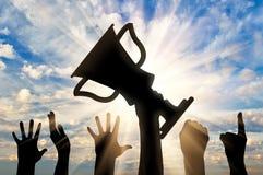 Silhouette d'une main tenant le trophée de championnat Image libre de droits