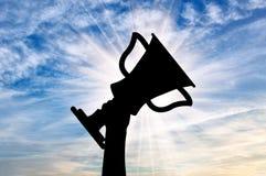 Silhouette d'une main tenant un trophée de championnat Image stock