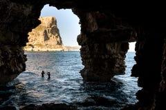 Silhouette d'une plongée d'homme dans l'eau, vue d'une caverne Photos libres de droits