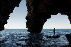 Silhouette d'une plongée d'homme dans l'eau, vue d'une caverne Photos stock