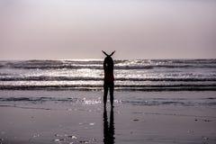 Silhouette d'une position de fille dans ressacs avec des mains vers le haut de former des ailes d'oiseau photographie stock