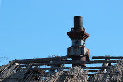 Silhouette of damaged old straw thatched roof with a chimney Stock Photo