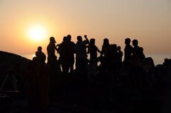 Silhouette dance team people. sunset on the sea. Silhouette of group of people dancing at sunset near the sea Royalty Free Stock Photos