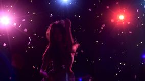 Silhouette of dancing girl with disco style lights and confetti. Silhouette of a dancing girl with long hair on a black background with disco style lights and stock footage
