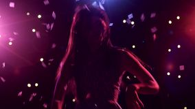 Silhouette of dancing girl with disco style lights and confetti. Silhouette of a dancing girl with long hair on a black background with disco style lights and stock video footage
