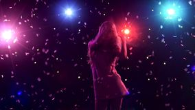 Silhouette of dancing girl with disco style lights and confetti. Silhouette of dancing girl with long hair in a short dress on black background with disco style stock video footage
