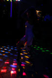 Silhouette of a dancing girl in a white dress in the night club Stock Photo