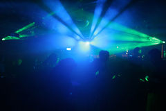 Silhouette of dancing people. Between green and blue scanner lights royalty free stock images