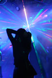 Silhouette of a dancing woman. In front of laser beams in a disco royalty free stock images