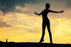Silhouette of dancing woman. Silhouette photo of dancing woman in modern pilates style over sunset landscape. Yoga royalty free stock images