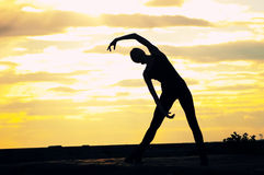 Silhouette of dancing woman over sunset. Yoga. Silhouette photo of dancing woman in modern pilates style over sunset landscape. Yoga stock images