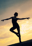 Silhouette of dancing woman over sunset. Yoga. Silhouette photo of dancing woman in modern pilates style over sunset landscape. Yoga royalty free stock photo