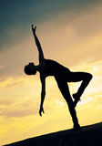 Silhouette of dancing woman over sunset. Yoga. Silhouette photo of dancing woman in modern pilates style over sunset landscape. Yoga stock photos