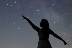 Silhouette of a dancing woman pointing in night sky. Woman Silhouette under starry night, Defocused Milky Way galaxy. Stock Image