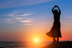 Silhouette of dancing woman on the sea coast during sunset. Silhouette of dancing woman on the sea coast during amazing sunset Royalty Free Stock Photo