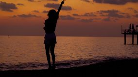 Silhouette of dancing woman on shoreline of ocean in sundown. Anonymous black silhouette of woman dancing on tropical beach in sunset light stock video footage