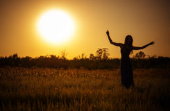 Silhouette of dancing girl against the sunset sky Royalty Free Stock Photography