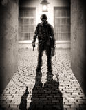 Silhouette of a dangerous military men. Horror. silhouette of a dangerous military man holding hand gun in the alley by the light of a lantern at night Royalty Free Stock Images