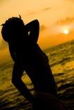 Silhouette dans le coucher du soleil Image stock
