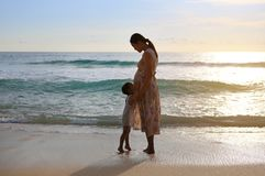 Silhouette daughter embracing pregnant mother relaxing on the beach at sunset stock photography