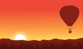 Silhouette de ballon à air chaud sur le ciel orange Image libre de droits