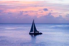 Silhouette de bateau dans l'océan au coucher du soleil Photographie stock