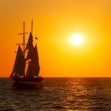Silhouette de bateau de navigation dans le coucher du soleil sur la mer Photos stock