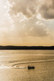 Silhouette de bateau de pêche sur le lac - lever de soleil/coucher du soleil d'or photographie stock
