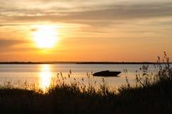 Silhouette de bateau par coucher du soleil Photo stock