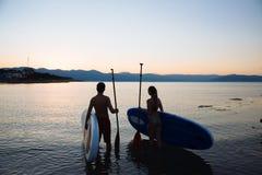 Silhouette de beaux ajouter au ressac et à la palette de petite gorgée à l'océan Mode de vie de concept, sport, amour Images stock