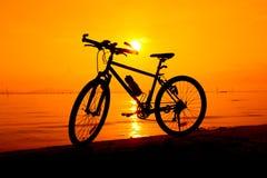 Silhouette de bicyclette sur la plage contre le coucher du soleil coloré en Th Photo stock