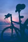 Silhouette de bicyclette sur la plage contre le coucher du soleil coloré en Th Images libres de droits