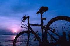 Silhouette de bicyclette sur la plage contre le coucher du soleil coloré en Th Images stock