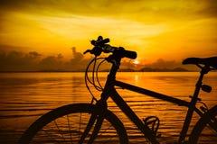 Silhouette de bicyclette sur la plage contre le coucher du soleil coloré en Th Photos libres de droits