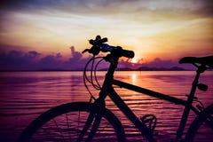 Silhouette de bicyclette sur la plage contre le coucher du soleil coloré en Th Image stock