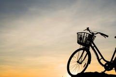 Silhouette de bicyclette sur un fond du coucher du soleil Image stock