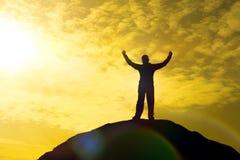 Silhouette de bonheur de succès de célébration de l'homme sur un fond de coucher du soleil de ciel de soirée de dessus de montagn Image stock
