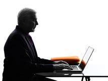 Silhouette de calcul sérieuse supérieure d'ordinateur portable d'homme d'affaires Photographie stock libre de droits