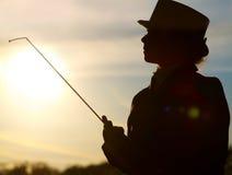 Silhouette de cavalier de femme avec un fouet dans les lumières d'un soleil Image libre de droits