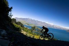 Silhouette de cavalier de vélo de montagne à Queenstown image libre de droits