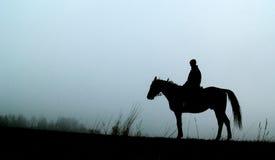 Silhouette de cheval avec l'homme Photos stock