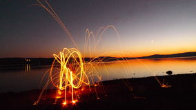 Silhouette de chute par le lac avec la peinture de lumière du feu Images stock