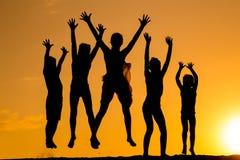 Silhouette de cinq enfants sautants contre le coucher du soleil Image libre de droits