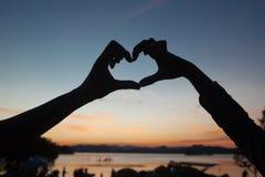 Silhouette de coeur de signe de main sur le ciel crépusculaire après coucher du soleil avec Image stock