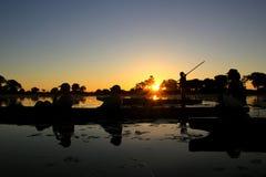 Silhouette de conduite de bateau de coucher du soleil Images stock