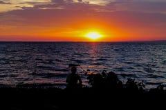 Silhouette de coucher du soleil d'un homme s'asseyant au rivage de lac Photo libre de droits