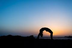 Silhouette de coucher du soleil de femme et de pont de yoga Image libre de droits